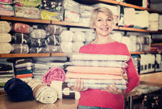 Smiling senior seller is showing wide assortment of bed linen. In a textile store Royalty Free Stock Photos