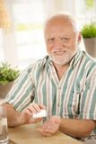 Smiling senior taking medication Stock Photo