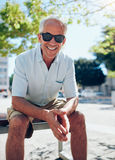 Smiling senior tourist sitting outdoors in the city Stock Image