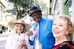 Free Smiling Senior Trio Eating Tasty Mexican Street Food Stock Photos - 160661493