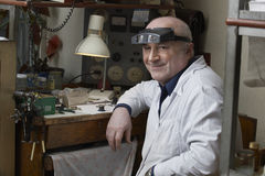 Smiling Senior Watch Repairman In Workshop Royalty Free Stock Photography