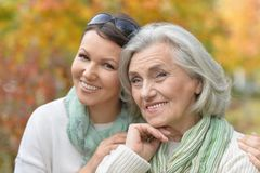 Close up portrait of senior woman with adult daughter in autumnal park stock images