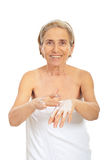 Smiling senior woman apply cream on hands Royalty Free Stock Image