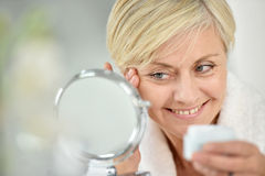 Smiling senior woman applying anti-aging cream Royalty Free Stock Photography