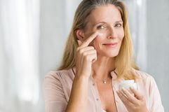 Woman applying anti aging lotion on face. Smiling senior woman applying anti-aging lotion to remove dark circles under eyes. Happy mature woman using cosmetic royalty free stock photo