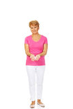Smiling senior woman with breast cancer awareness ribbon Royalty Free Stock Images