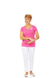 Smiling senior woman with breast cancer awareness ribbon Royalty Free Stock Image
