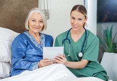Smiling Senior Woman And Caretaker Holding Tablet. Portrait of smiling senior women and female caretaker holding tablet PC in bedroom at nursing home royalty free stock photography