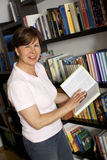 Smiling senior woman carrying books Royalty Free Stock Images