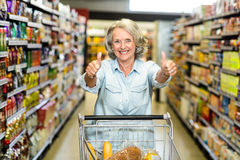 Smiling senior woman with cart showing thumbs up Stock Photography