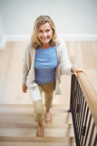 Smiling senior woman climbing upstairs at home royalty free stock photography