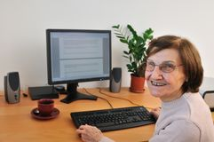 Smiling senior woman at computer Stock Images