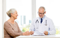 Smiling senior woman and doctor meeting Stock Images