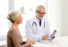 Smiling senior woman and doctor with tablet pc Stock Image