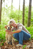 Smiling senior woman with dog in forest Royalty Free Stock Photos