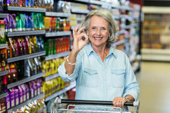 Smiling senior woman doing ok sign with hand. At the supermarket royalty free stock photography