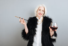 Smiling senior woman drinking wine and smoking. Royalty Free Stock Images