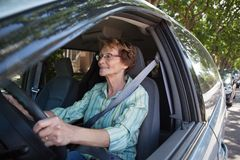 Smiling senior woman driving car stock images