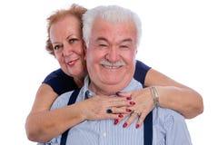 Smiling senior woman embracing her husband Stock Photo