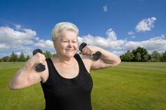 Smiling senior woman exercising with dumbells in park