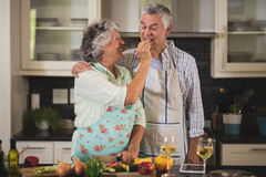 Smiling senior woman feeding man while standing in kitchen Royalty Free Stock Photography