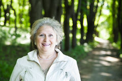 Smiling senior woman in forest Stock Image