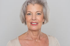 Smiling senior woman. In front of grey background Stock Photography
