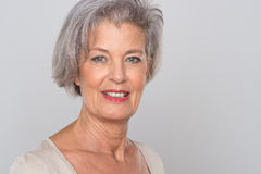 Smiling senior woman. In front of grey background Royalty Free Stock Photos