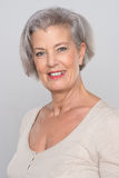 Smiling senior woman. In front of grey background Royalty Free Stock Photo