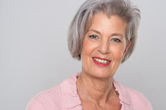 Smiling senior woman. In front of grey background Royalty Free Stock Images