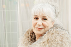 Smiling senior woman in fur coat Stock Images