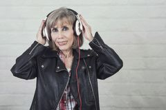 Smiling senior woman with headphones listening to music. On brick background royalty free stock photography