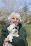Smiling Senior woman with her dog in the spring park Royalty Free Stock Photo