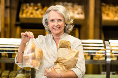 Smiling senior woman holding bags with bread Stock Photography