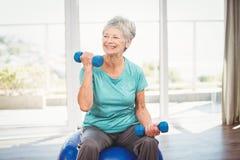 Smiling senior woman holding dumbbell Stock Photo