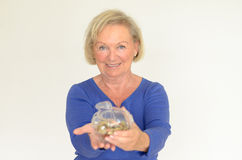 Smiling senior woman holding a glass piggy bank. Filled with loose coins extended in her hands - her nest-egg for a dream purchase Royalty Free Stock Photo