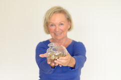 Smiling senior woman holding a glass piggy bank. Filled with loose coins extended in her hands - her nest-egg for a dream purchase Royalty Free Stock Photos