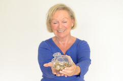 Smiling senior woman holding a glass piggy bank Royalty Free Stock Photo