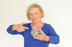 Smiling senior woman holding a glass piggy bank. Filled with loose coins extended in her hands - her nest-egg for a dream purchase Stock Image