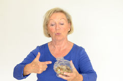Smiling senior woman holding a glass piggy bank Stock Images