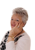 Smiling senior woman holding hand on face. Stock Photography