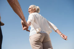 Smiling senior woman holding hand of senior man and walking outdoors Stock Images