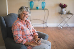 Smiling senior woman holding mobile phone while sitting on armchair at home Royalty Free Stock Photography
