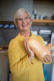 Smiling senior woman holding squash in kitchen Stock Image