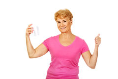 Smiling senior woman holding a tooth model and showing thumb up Stock Photo