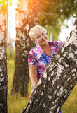 Smiling senior woman holding tree trunk in park Royalty Free Stock Photo