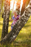 Smiling senior woman holding tree trunk in park Stock Images