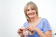 Smiling senior woman knitting Stock Image
