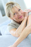 Smiling senior woman leaning on sofa Royalty Free Stock Photography