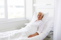 Smiling senior woman lying on bed at hospital ward stock photos
